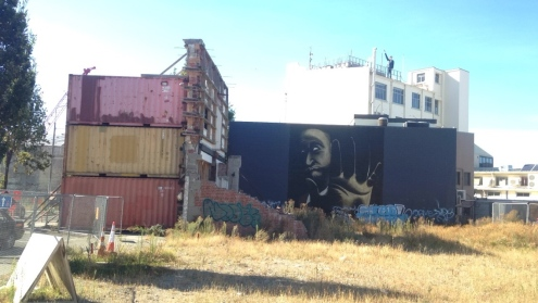 Chch Street art and old brick building frames being held up by containers